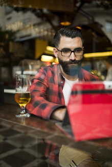 Adult bearded hipster style man touching tablet in bar and drinking alchohol near to window - JASF000020