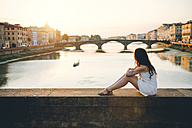 Italy, Florence, woman wearing white summer dress sitting on a bridge at sunset - GEMF000324