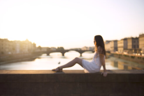 Italy, Florence, woman wearing white summer dress sitting on a bridge at sunset - GEMF000329