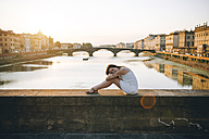 Italy, Florence, woman wearing white summer dress sitting on a bridge enjoying the sunset - GEMF000330