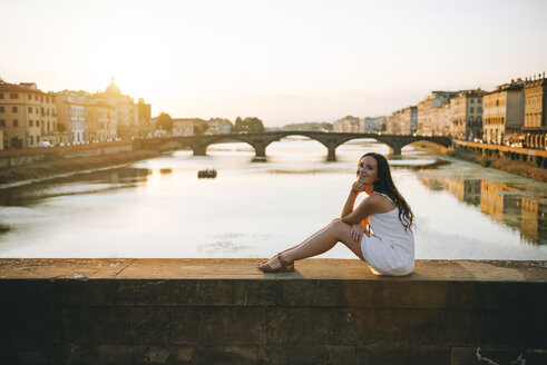 Italy, Florence, happy woman sitting on a bridge at sunset - GEMF000332