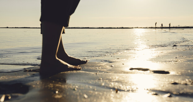 Woman standing barefoot at seashore by evening twilight, close-up - GEMF000333