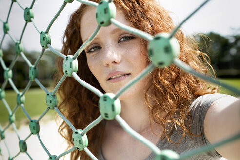 Portrait of redheaded teenage girl looking through net - GDF000859