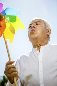 Senior man blowing against pinwheel outdoors - RKNF000175