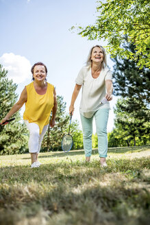 Two happy mature women on a meadow playing badminton - RKNF000185
