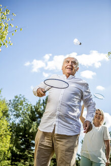 Happy elderly couple playing badminton outdoors - RKNF000187