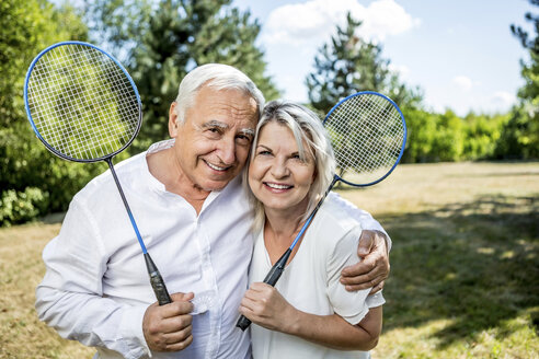 Portrait of smiling elderly couple on a meadow holding badminton rackets - RKNF000190