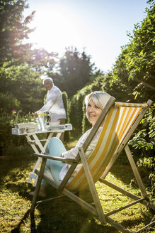 Mature woman in deckchair in garden with man in background - RKNF000228