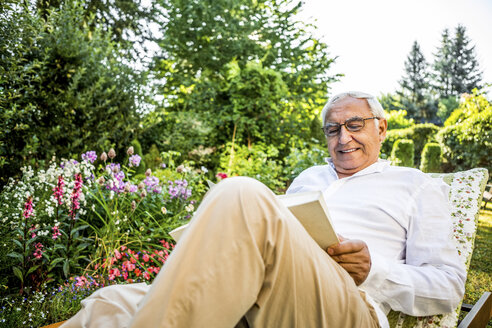 Smiling senior man reading book in garden - RKNF000238