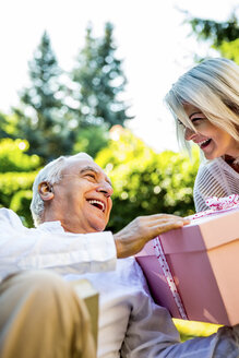 Happy elderly couple with large present outdoors - RKNF000240