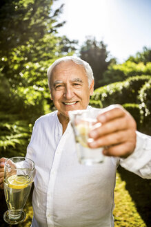 Smiling senior man holding glass of water in garden - RKNF000248