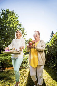 Two happy mature women carrying apples and tray in garden - RKNF000252