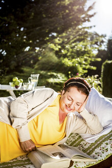 Smiling mature woman reading book on garden lounge - RKNF000254