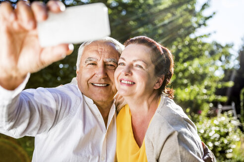 Happy elderly couple taking a selfie outdoors - RKNF000265