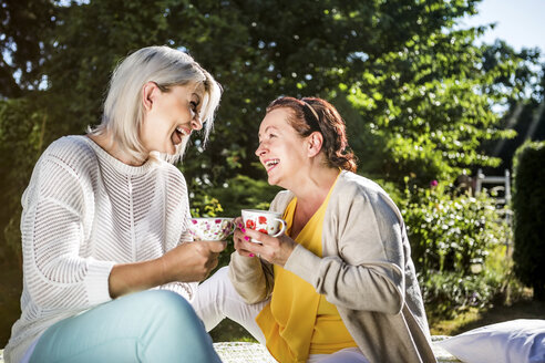 Happy mature women in garden with coffee cups - RKNF000269