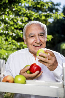 Smiling senior man holding apples outdoors - RKNF000286