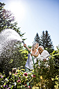 Smiling mature woman watering flowers in garden with man kissing her shoulder - RKNF000293