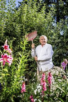 Senior man standing with rake in garden - RKNF000301
