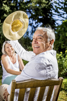 Happy senior man in garden with woman in background - RKNF000308