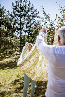 Elderly couple holding picnic blanket on a meadow - RKNF000317