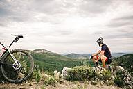 Spain, Tarragona, Mountain biker having a break in extreme terrain - JRFF000027