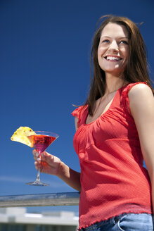 Smiling young woman in sunshine holding drink - TOYF001384