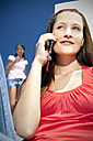 Smiling young woman on cell phone in sunshine - TOYF001336