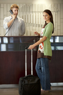 Woman standing at hotel reception with rolling suitcase - TOYF001387