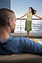 Young man on couch with girlfriend standing on balcony by the sea - TOYF001389