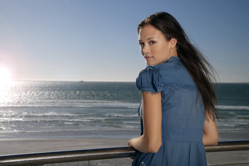 Young woman leaning on railing by the sea - TOYF001391