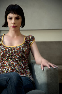 Portrait of young woman sitting in armchair - TOYF001358