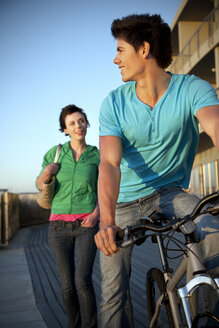 Young man with bicycle and woman following him - TOYF001395