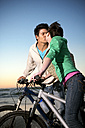 Young couple kissing on bicycles at the coast - TOYF001396