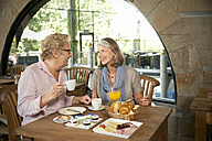 Smiling senior couple having breakfast in a cafe - TOYF001261