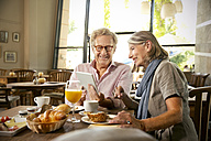 Smiling senior couple with digital tablet having breakfast in a cafe - TOYF001267