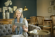 Smiling senior woman in lounge room using digital tablet - TOYF001273