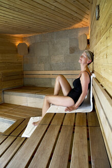 Senior woman relaxing in a sauna - TOYF001283