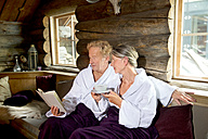 Senior couple sitting on bench in bathrobes reading a book and drinking tea - TOYF001286
