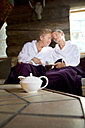 Relaxed senior couple sitting on bench in bathrobes with teapot in foreground - TOYF001289