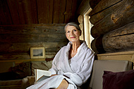Smiling senior woman sitting on bench in bathrobe with a book - TOYF001292