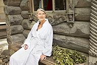 Smiling senior woman in bathrobe sitting outside Finnish sauna log cabin - TOYF001295