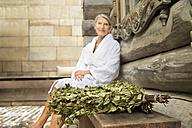 Senior woman in bathrobe sitting outside Finnish sauna log cabin with twigs in foreground - TOYF001298