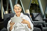 Senior woman in bathrobe sitting in armchair using digital tablet - TOYF001307
