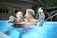 Happy senior couple in swimming pool at a spa - TOYF001316
