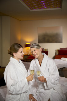 Happy senior woman and adult daughter in bathrobes clinking champagne glasses - TOYF001319