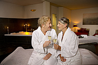Smiling senior couple in bathrobes clinking champagne glasses - TOYF001322