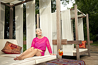 Smiling senior woman sitting on lounge outdoors with cocktail - TOYF001329