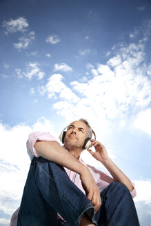 Portrait of man hearing music with headphones in front of clouded sky - TOYF001173