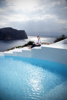 Spain, Mallorca, woman with laptop sitting on stairs besides a swimming pool with the sea in the background - TOYF001179
