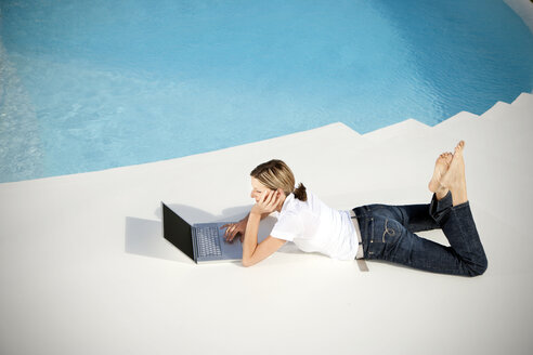 Spain, Mallorca, woman lying besides a swimming pool looking at   laptop - TOYF001185